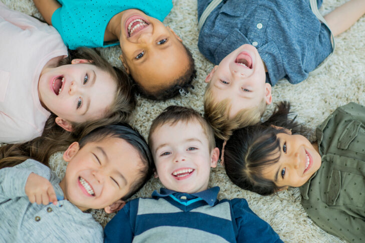 A multi-ethnic group group of young children lay down in a circle on a living room carpet with their heads together all brightly smiling at the camera.