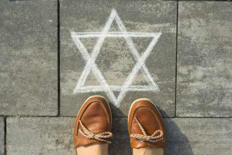 Female feet with abstract image of six pointed star, written on grey sidewalk.