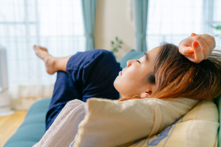 A young woman is lying down on a sofa and resting in the living room at home.