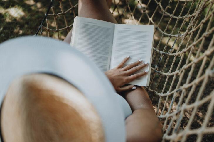 Woman reading book in hammock