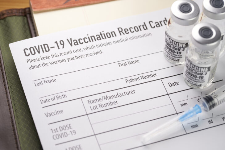 Covid-19 vaccination record card with vials and syringe.