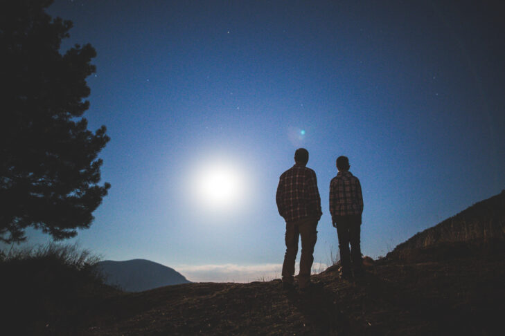 Photo of father with son in nature at night