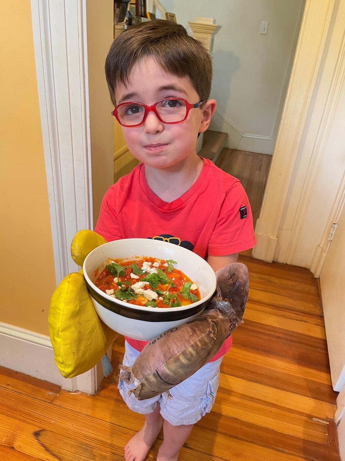 Kara's son Peter holds the finished shakshuka (Photo: Kara Baskin)