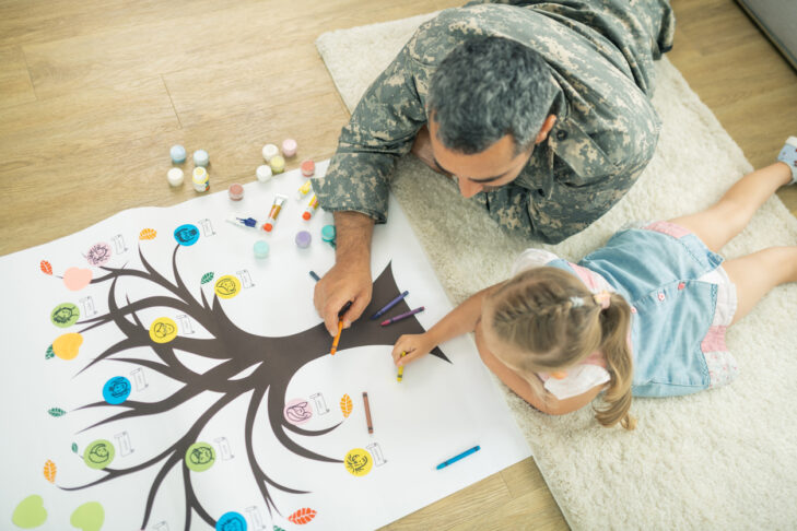 Lying on floor. Top view of caring father and daughter lying on the floor and painting family tree