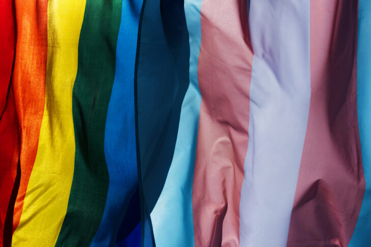 closeup of a gay pride flag and a transgender pride flag waving on the blue sky, moved by the wind