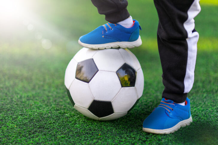 Children's foot of the winner in sports shoes sneaker stands on a soccer ball against a background of grass. Close-up street shot of game and training with victory.