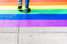 Feet Walking on Sidewalk Decorated with Rainbow Flag. Lesbian, Gay, Bisexual, Pansexual, Asexual, Queer, LGBTQ and LGBTQ plus concepts
