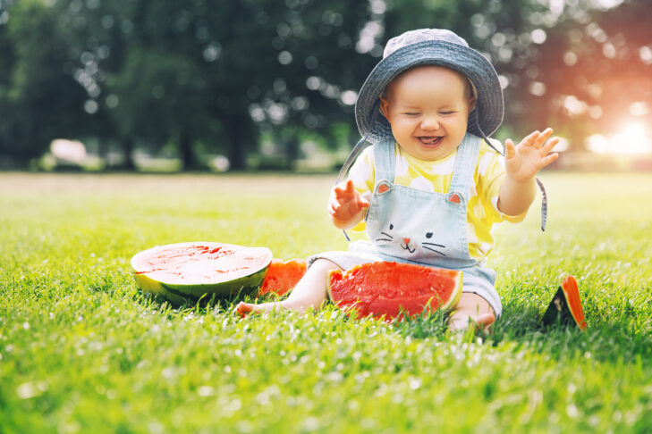 Cutest smiling baby girl eating watermelon on green grass in summertime. Funny happy little kid eats healthy fruit snack on nature. Image of Childhood, Family, Baby Feeding.