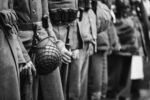 Close Up Of German Military Ammunition Of A German Soldier. Unidentified Re-enactors Dressed As World War II German Soldiers Standing Order. Photo In Black And White Colors. Soldiers Holding Weapon Rifles