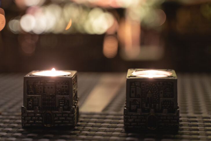 Silver candles lights on Friday night dinner for popular Shabbat meal. Jewish day of rest tradition with bokeh lights effect on background