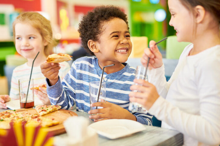 Colorful portrait of multi-ethnic group of children eating pizza enjoying awesome  party in cafe, focus on African-American boy laughing happily