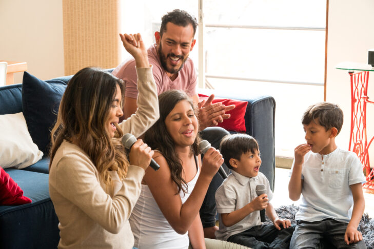 Latin family singing karaoke laughing and enjoying all together in the living room of his house