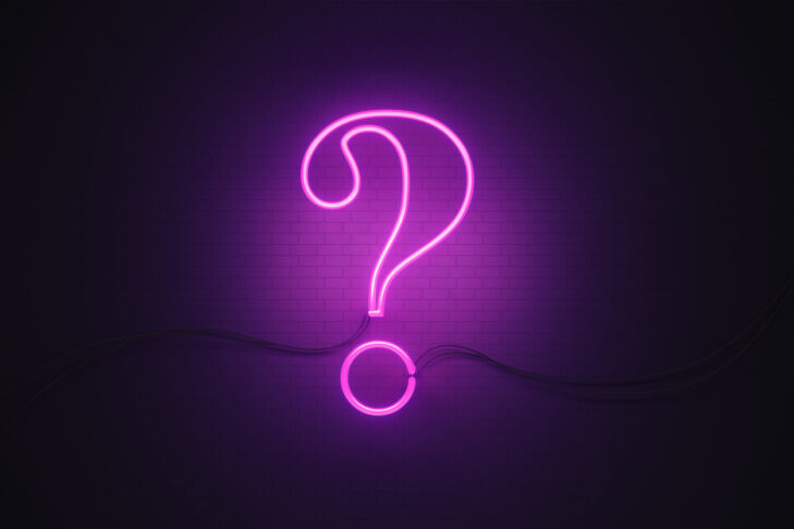 Question mark symbol drawn by purple neon light on black wall. Horizontal composition with copy space.