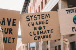 Group of people participating in a protest against global warming. Climate change protest concept. They are holding banner signs.