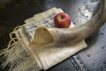 Close up of shofar ,Hebrew prayer book  and apple on a table- symbols for