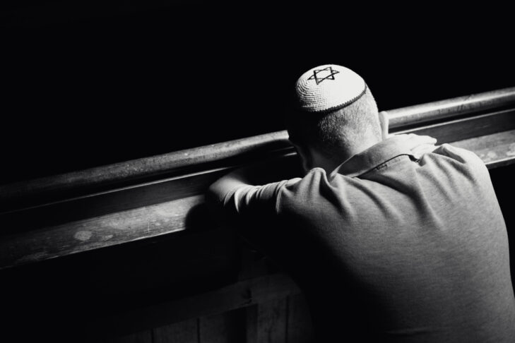 Monochrome image depicting a young Jewish adult man in his 30s inside a synagogue. He has his head bowed in prayer and he is wearing the traditional Jewish skull cap - otherwise known as a kippah or yarmulke - on his head. The man has a beard and the background of the synagogue is blurred out of focus. Horizontal color image with copy space.