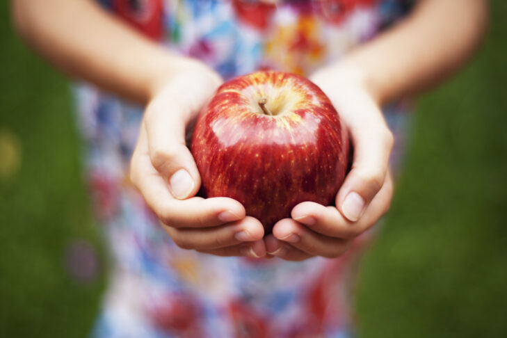 A girl holding a bright red apple.