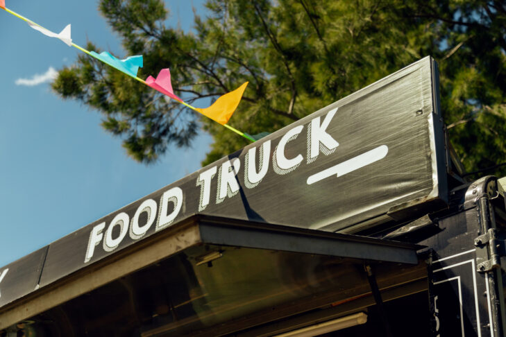 Signboard of a food truck with colorful pennants