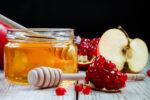 Jewish religious holiday Rosh Hashanah. Still life of apples, pomegranates and honey on a dark wooden background. Traditional symbols of celebration