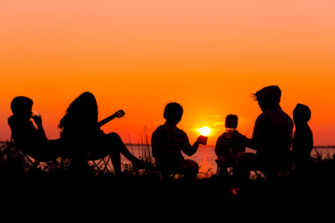 Silhouette of group of people sitting on the beach with campfire at sunset
