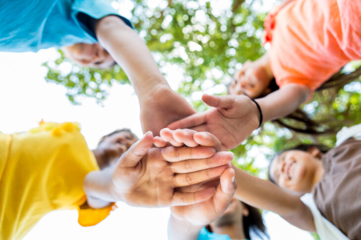 Diverse active school kids have their hands together in a circle. They are playing together at the park or school or they are at a sporting event. They are wearing bright colors. Photo shot from low angle viewpoint looking up at their hands. Focus is on the hands. Their faces and trees are blurred. It is a bright sunny day.